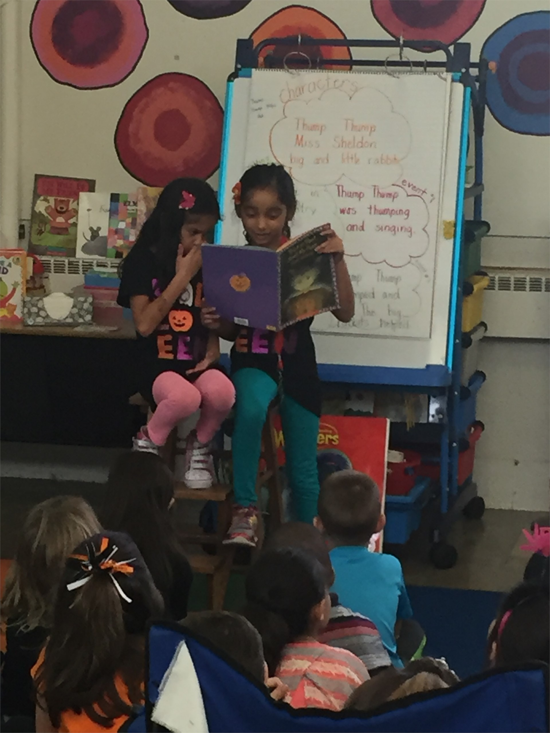 Amiya and Arya B. Sister Principals for the day reading to students.