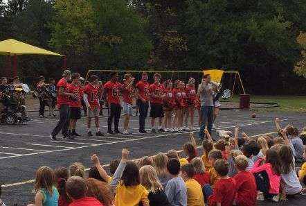 Football players and cheerleaders at pep rally