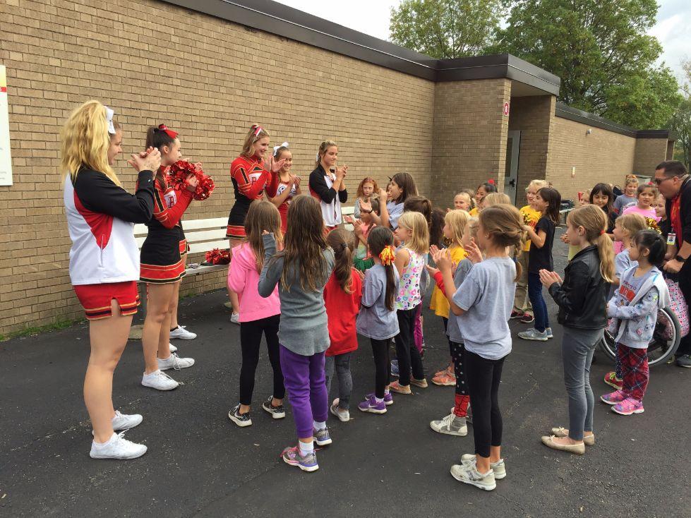 Cheerleaders teaching cheers at pep rally