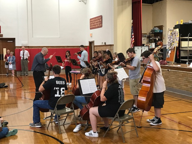 High School students demonstrating orchestra instruments