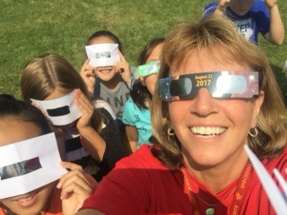 Teacher and students looking at the eclipse